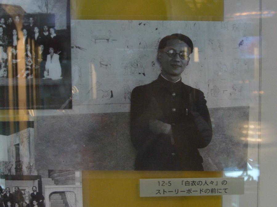 ストーリーボードの前に立つ学生時代の手塚治虫