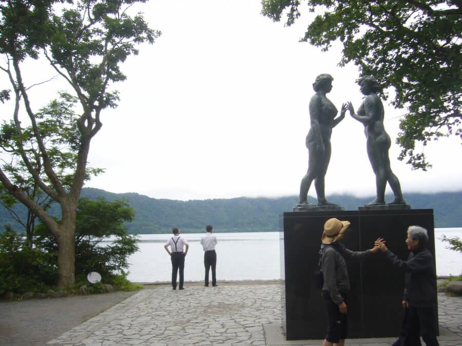 乙女の像で記念撮影する人たち